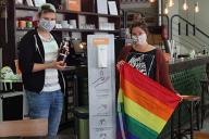 Zwei Mitarbeiter*innen des anyway stehen mit Desinfektionsmittel und Regenbogenflagge vor einem Desinfektionsspender im Café.