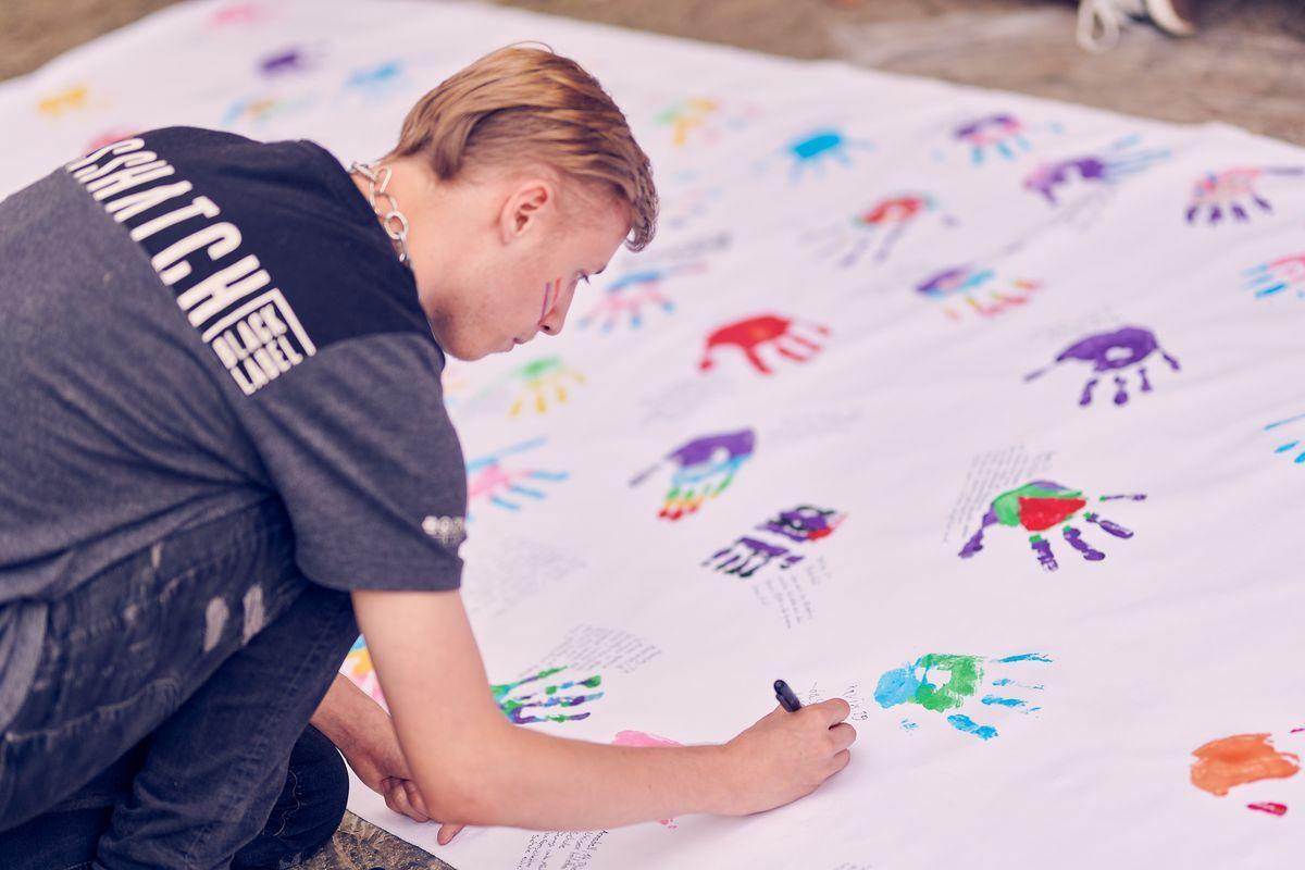Jugendlicher beschriftet Banner mit Farbabdruck seiner Hand , Foto: Marius Steffen, www.mariussteffen.de