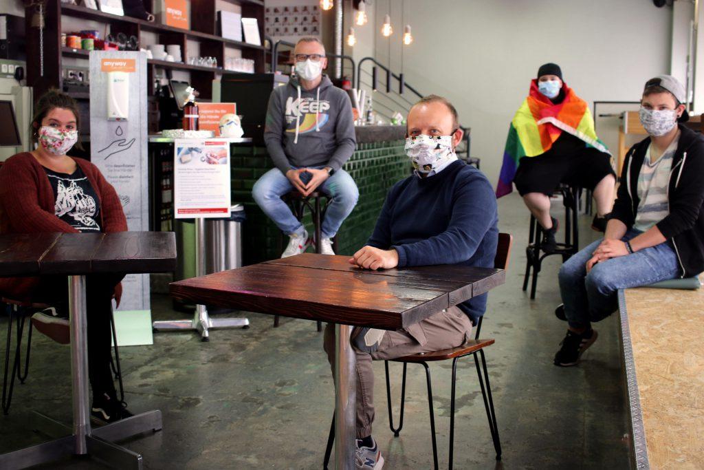 Mitarbeiter*innen des anyway sitzen mit Maske und Abstand im Café.